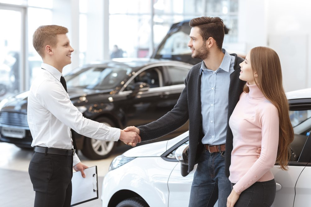 Couple asking about qualifying for a Dealer Purchased Car Loan